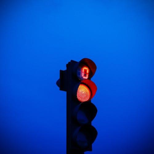 Red traffic light against blue sky