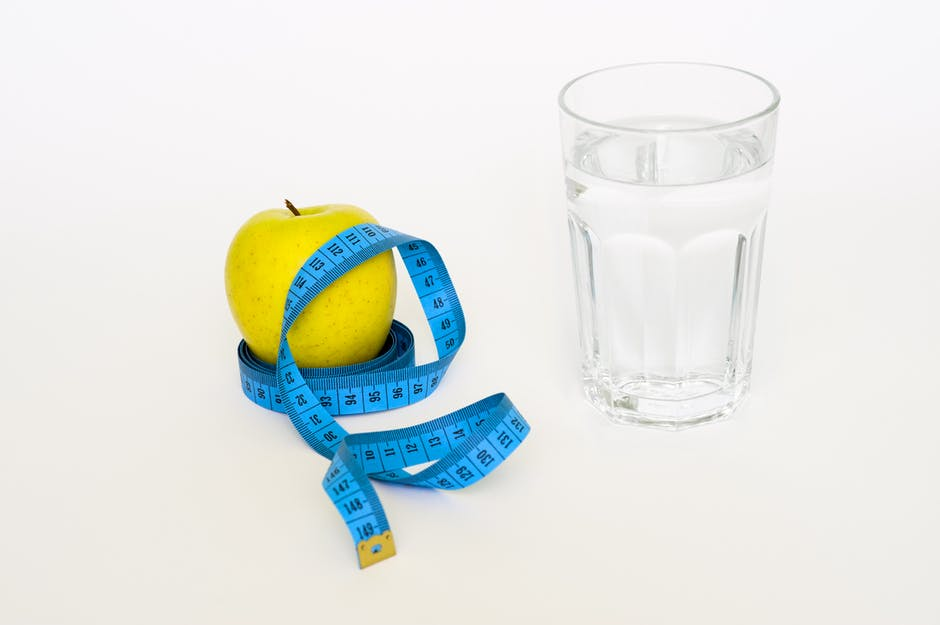 Clear Drinking Glass Near in Blue Tape Measure and Apple Fruit