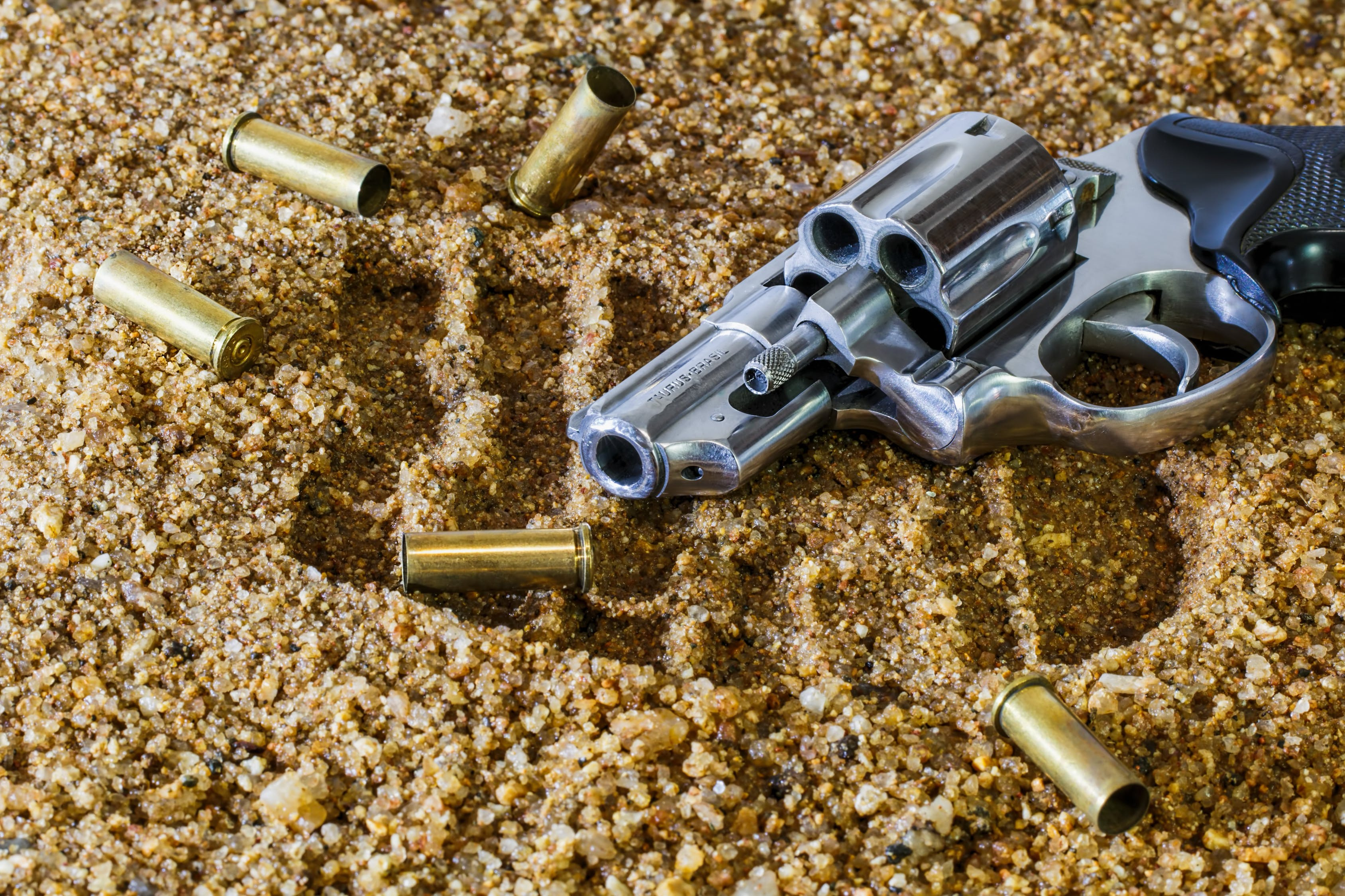 Gun on a sand near a bullets