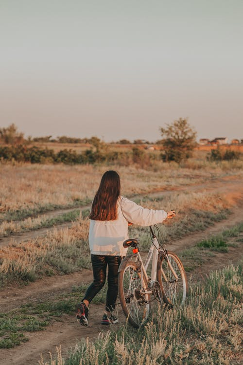 Back view of faceless lady with dark hair rolling bicycle on grassy road in countryside in summer evening in nature