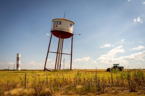 Brown Water Tank on Green Grass Field Under Blue Sky
