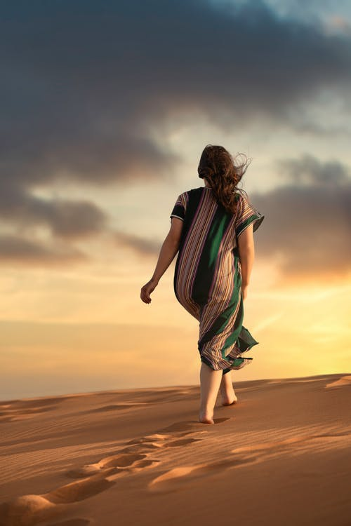 Woman in Black White and Green Stripe Dress Walking on Brown Sand