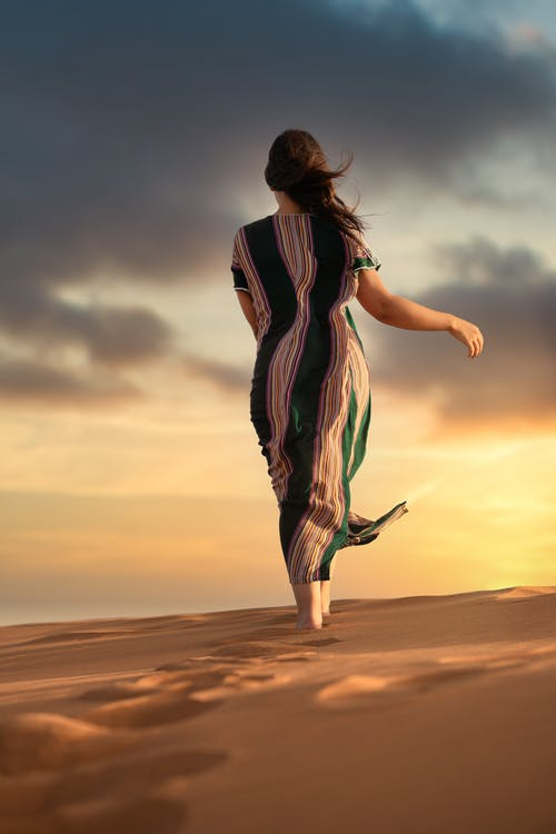 Woman in Black and White Stripe Dress Standing on Brown Sand during Sunset