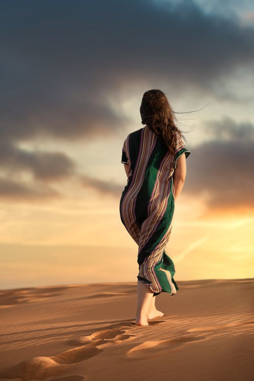 Woman in Green and Black Dress Standing on Brown Sand during Sunset
