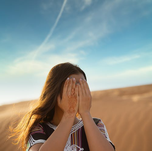 Woman in Black and White Stripe Shirt Covering Her Face With Her Hands