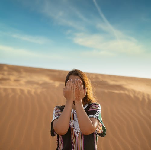 Woman in Black and White Stripe Shirt Standing on Brown Sand