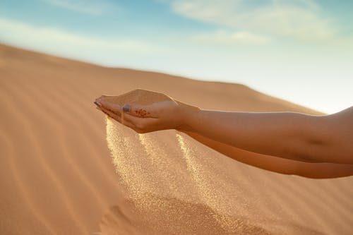 Person Holding Brown Sand in Desert