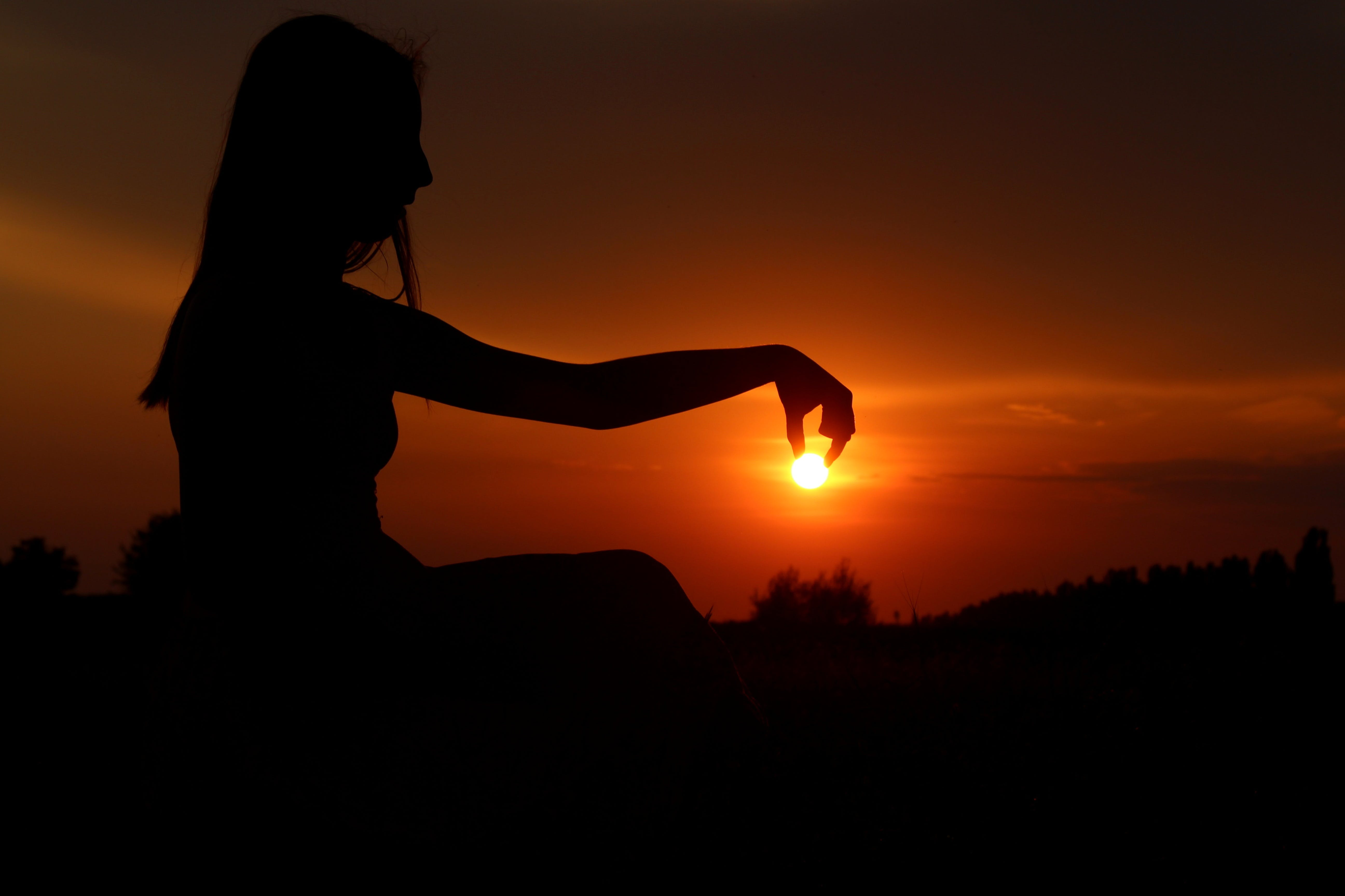 Force Perspective Photography of Woman Picking Sun