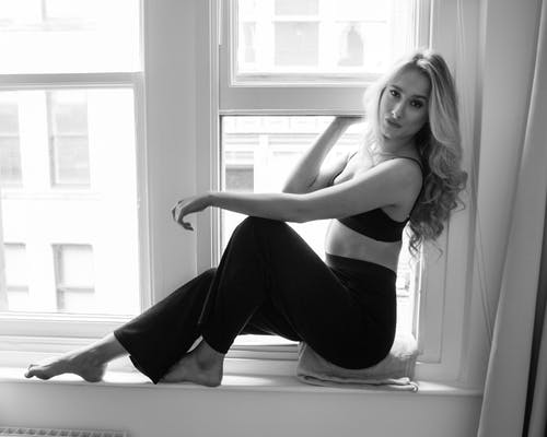 Woman in Black Tank Top and Black Pants Sitting on White Bathtub