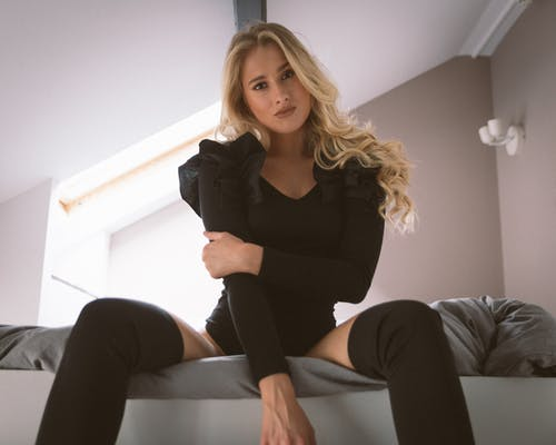 Woman in Black Long Sleeve Shirt and Black Pants Sitting on White Couch