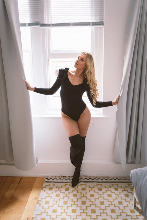 Woman in Black Long Sleeve Shirt and Black Stockings Standing Beside White Window Curtain