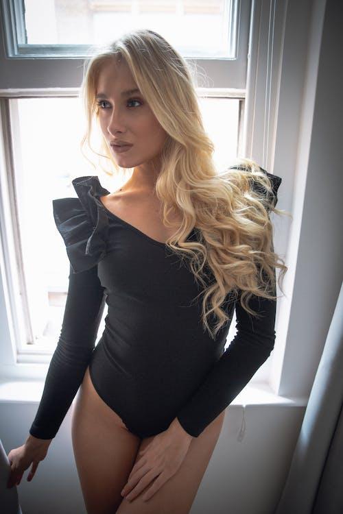 Woman in Black Long Sleeve Shirt Standing Near Window