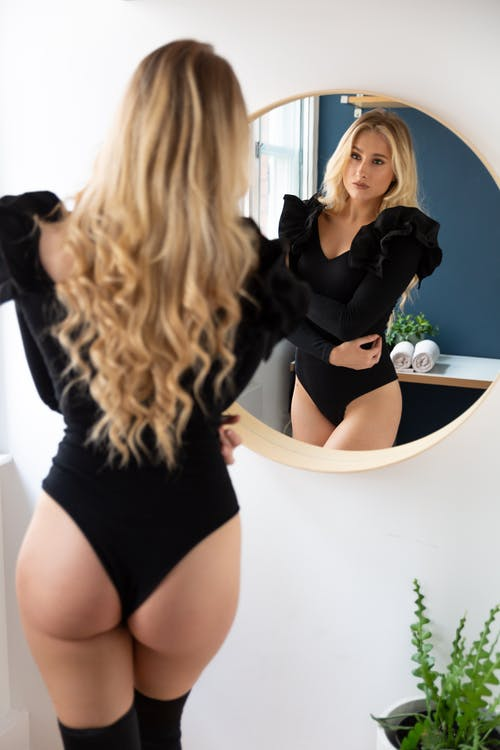 Woman in Black Long Sleeve Shirt and Black Panty Standing Beside White Ceramic Sink