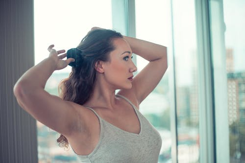 Woman in White Tank Top Holding Her Hair