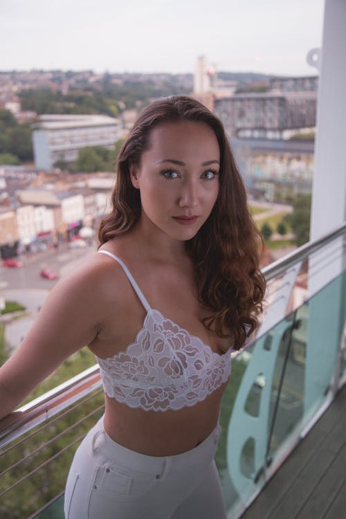 Woman in White Floral Brassiere Standing Beside Railings