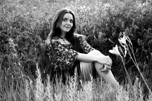 Grayscale Photography of Woman Sitting on Grass