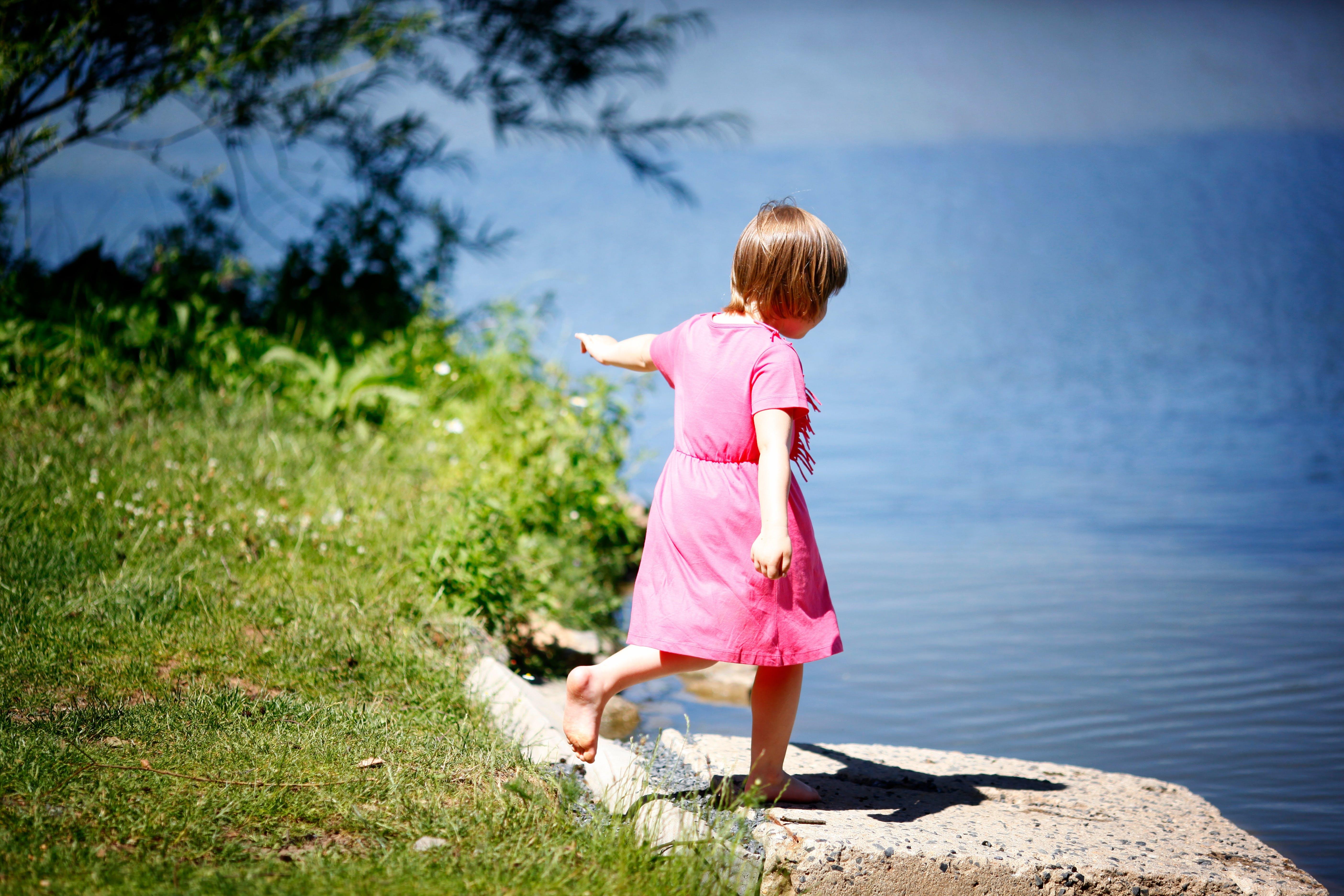 Child Standing Near Body of Water
