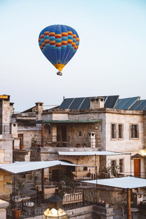 Yellow Blue and Red Hot Air Balloon Flying over Brown Concrete Building