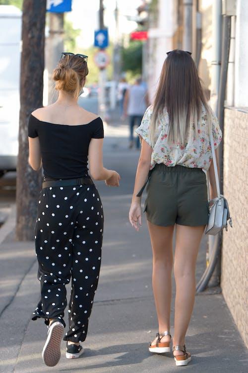 Woman in Black and White Polka Dots Dress Walking on Sidewalk