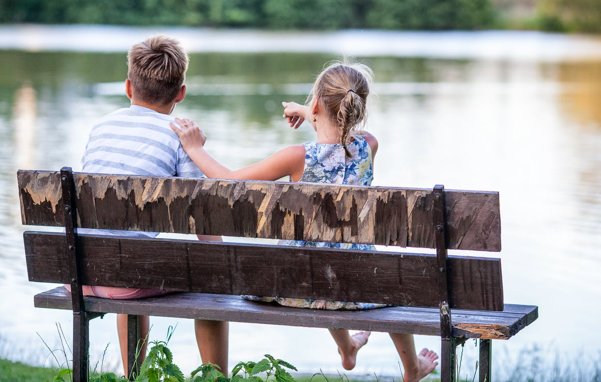 Selective Focus Photography of Boy and Girl Sitting on Bench Near Lake