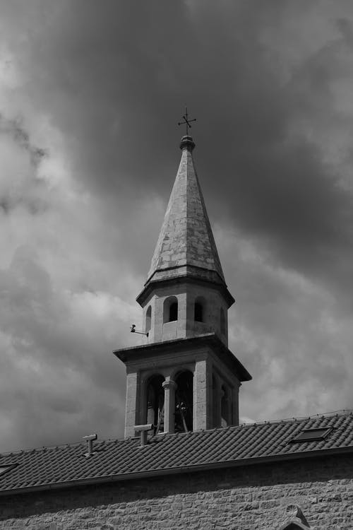 Grayscale Photo of Church Under Cloudy Sky