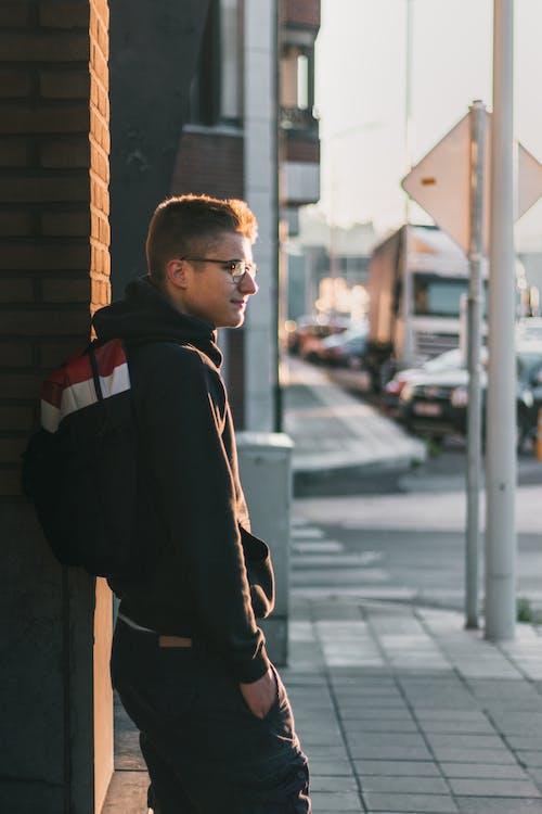 Man Standing Near Brown Brick Wall