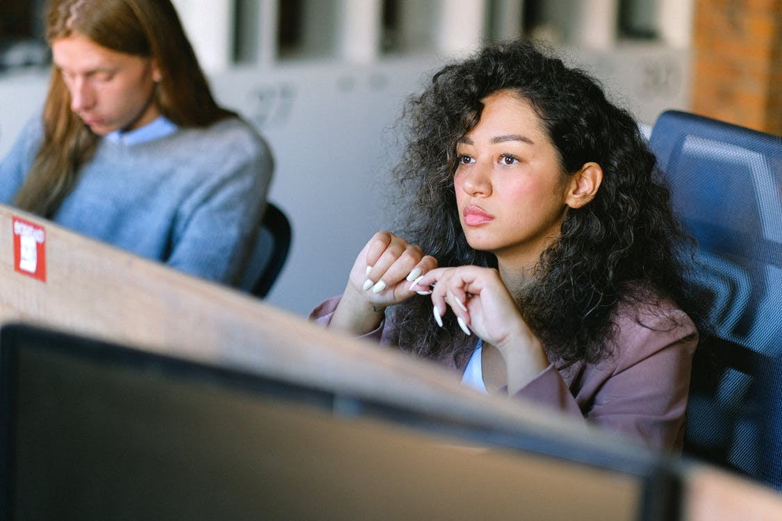 High angle of concentrated female employee sitting at table in open space and thoughtfully looking away