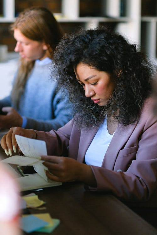 Serious woman looking through documents in office