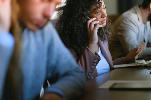 Serious woman talking on smartphone during work with colleagues