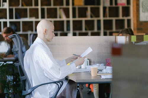 Focused woman reading papers in modern workplace