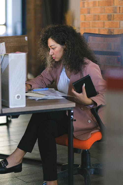 Concentrated woman with curly hair in formal clothes working with documents at table in modern workplace