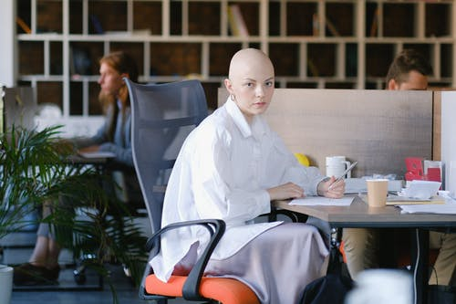 Focused bald female office employee sitting in modern open space and writing in document during work