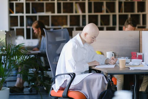 Side view of concentrated bald woman writing in paper document while working in office with colleagues