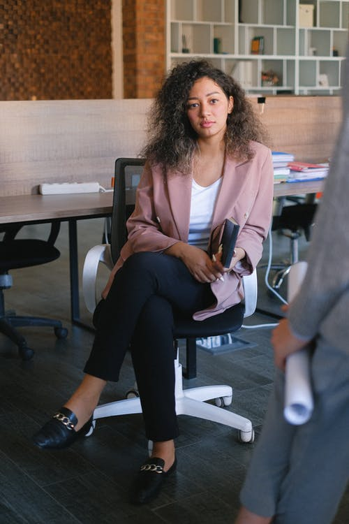 Full body of female manager listening to coworker report during business discussion in office