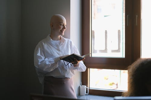 Positive bald female worker with notebook standing near window and explaining business project to coworker