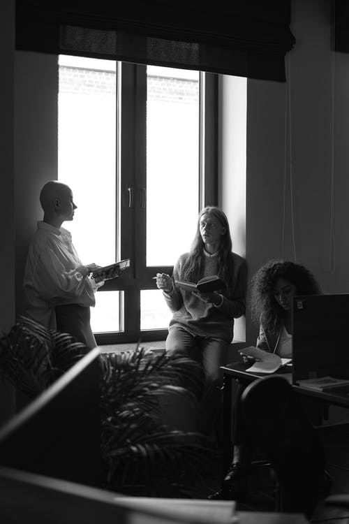 Black and white of man and women gathering together for meeting and business discussion in modern office