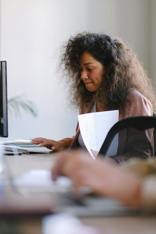 Side view of focused female with documents in hand browsing computer while working at table in office with blurred colleague