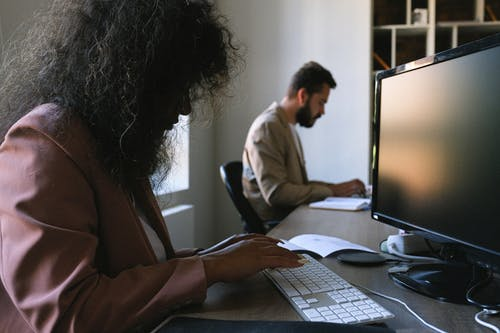 Coworkers working on computers in office