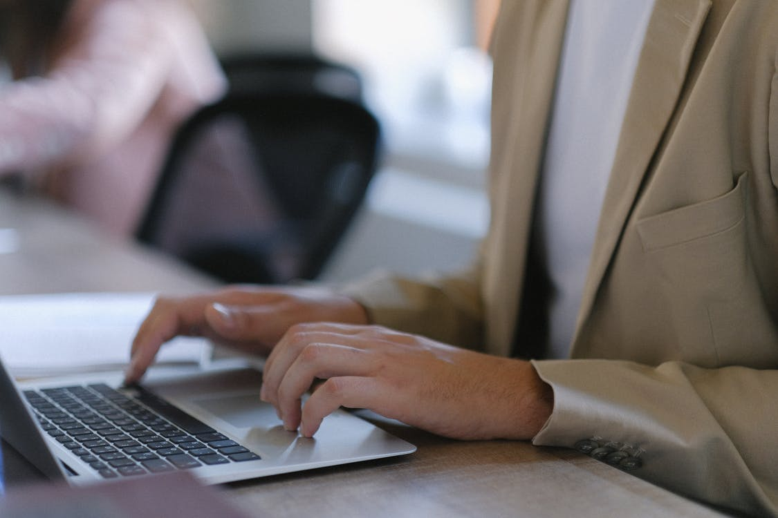 Unrecognizable male worker in formal wear browsing modern netbook while sitting at table during work in office with colleague on blurred background