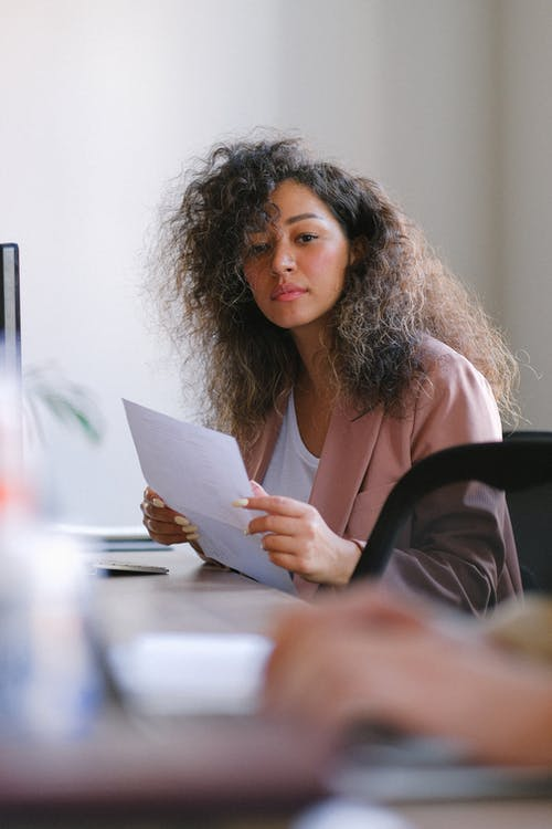 Thoughtful woman with documents working in office