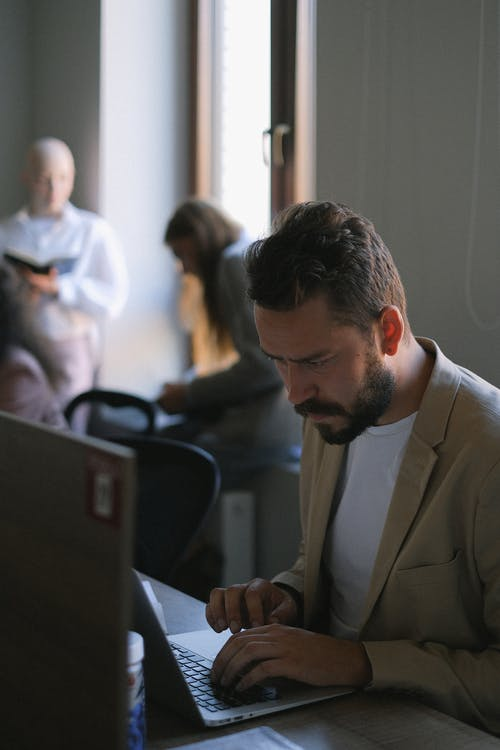 Focused man browsing laptop in office with people