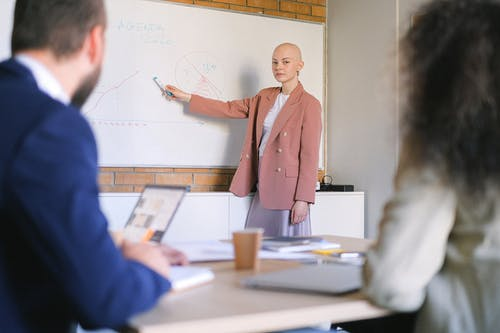 Bald woman showing graphics in office