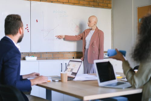Female manager demonstrating graphs on whiteboard to anonymous coworkers at table with laptops in conference room during meeting