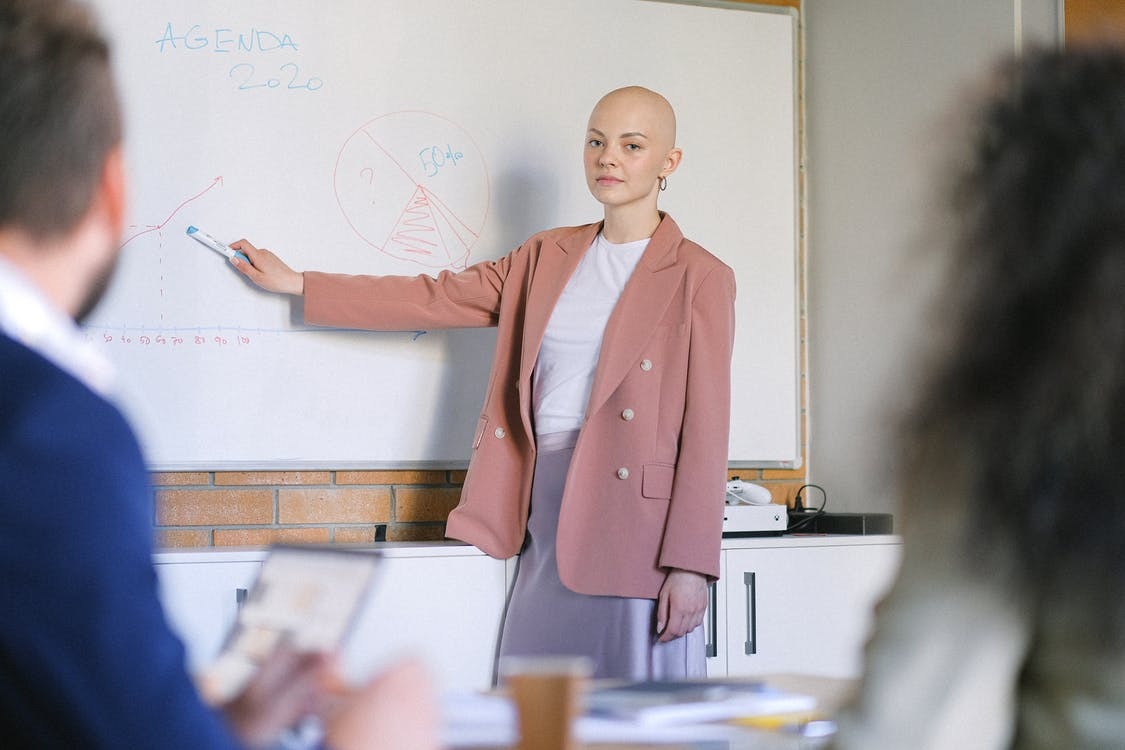 Content female looking at camera and pointing with marker at whiteboard with diagrams while explaining marketing plan to colleagues in conference room during briefing