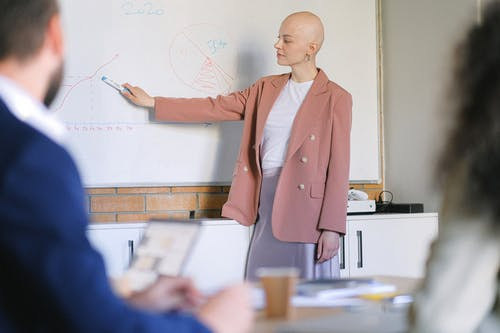 Bald female pointing at whiteboard with graphs and schemes in conference room with blurred colleagues during meeting