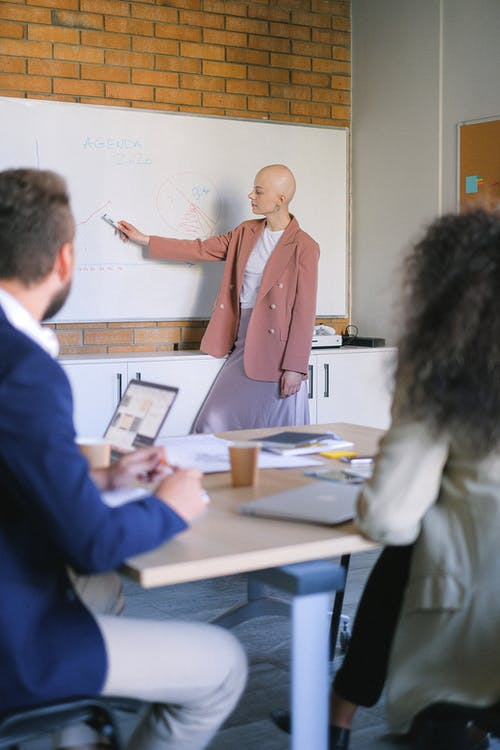 Busy bald female pointing with marker at board with diagrams while presenting new strategy to coworkers with laptop during meeting in office