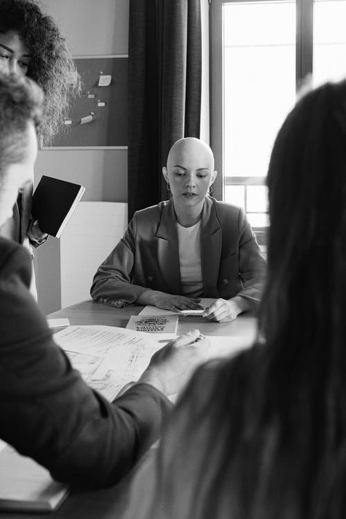 Black and white of focused female with unrecognizable colleagues gathering at table with documents during brainstorm in modern conference room