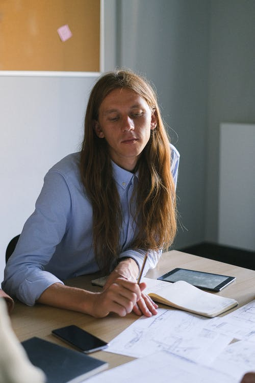 Pensive man with long hair working at table