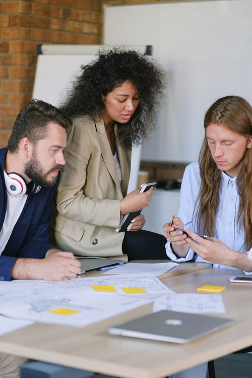 Group of diverse men and woman talking and using mobile phone at table with papers and table in office