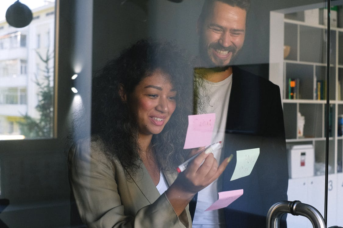 Diverse happy business partners checking stickers on glass door and smiling together in office